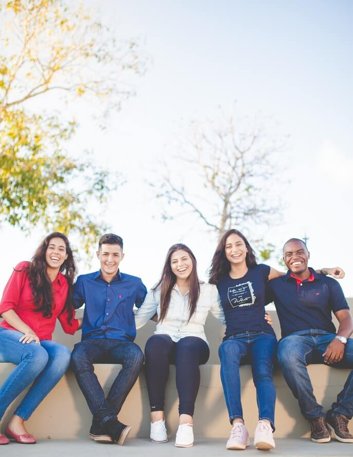 Image of five friends sitting down for a photo.