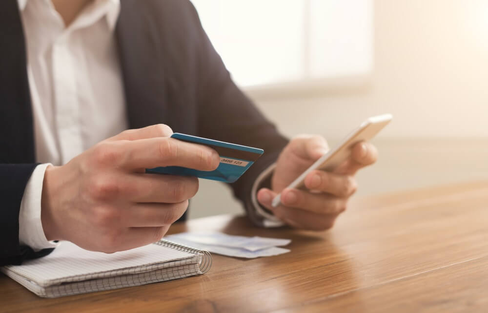 Image of a man holding up his smartphone and credit card.