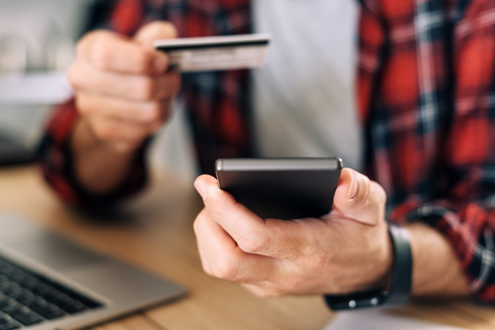 Online shopping from home office using smartphone and credit card, close up of male hands in e-commerce concept
