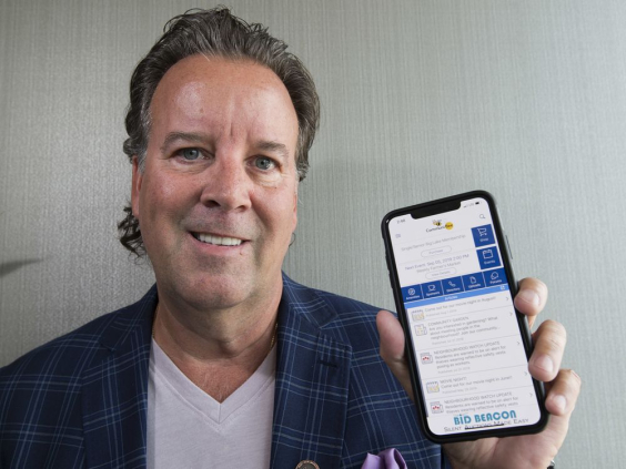Image of Graham Murray holding up his smartphone with CommuniBee open.